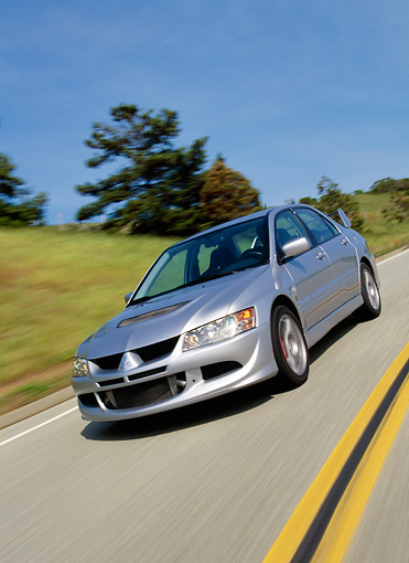 AUT 29 RK0638 38 © Kimball Stock 2003 Mitsubishi Lancer Evolution VIII Silver Slanted 3/4 Front View On Road In Motion
