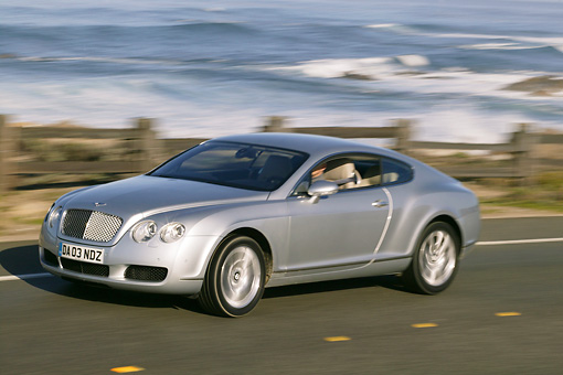 AUT 29 RK0669 01 © Kimball Stock 2004 Bentley Continental GT Silver 3/4 Side View On Road Beach Background