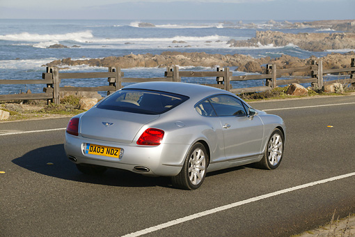 AUT 29 RK0670 01 © Kimball Stock 2004 Bentley Continental GT Silver 3/4 Rear View On Road Beach Background