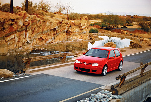 AUT 29 RK0676 06 © Kimball Stock 2005 Volkswagen R32 Golf Red 3/4 Front View Crossing Bridge By Rocks Filtered