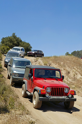 AUT 29 RK0801 01 © Kimball Stock 2004 Wrangler Jeep Red With Group Of Cars In Motion On Dirt Hill