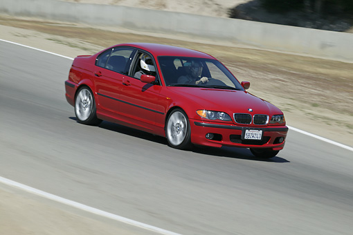AUT 29 RK0805 01 © Kimball Stock 2004 BMW 330i 3 Series Red Side 3/4 View On Road In Motion