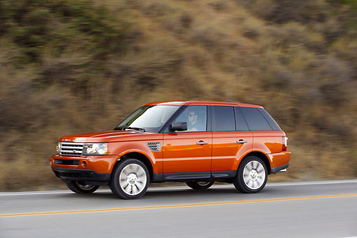 AUT 29 RK0859 01 © Kimball Stock 2006 Range Rover Sport Supercharged Orange 3/4 Side View On Road In Motion