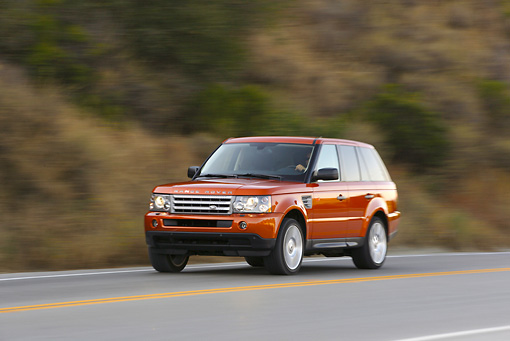 AUT 29 RK0875 01 © Kimball Stock 2006 Range Rover Supercharged Orange 3/4 Front View On Road In Motion