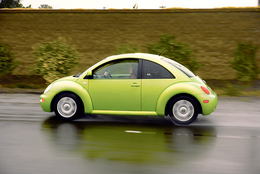 AUT 29 RK1157 01 © Kimball Stock 2005 VW Beetle Green Profile Shot On Wet Road In Motion