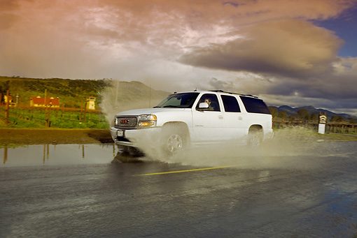 AUT 29 RK1164 01 © Kimball Stock 2005 GMC Yukon XL Denali White 3/4 Side View On Wet Road In Motion