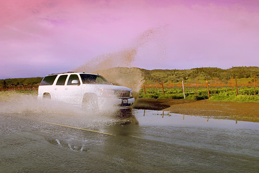 AUT 29 RK1165 01 © Kimball Stock 2005 GMC Yukon XL Denali White 3/4 Front View On Wet Road In Motion