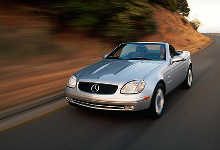 AUT 29 RK0003 01 © Kimball Stock 1998 Mercedes-Benz SLK Kompressor Silver 3/4 Front View On Road In Motion