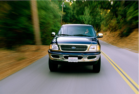 AUT 29 RK0006 03 © Kimball Stock 1997 Ford Expedition Blue Head On View On Road In Motion By Trees