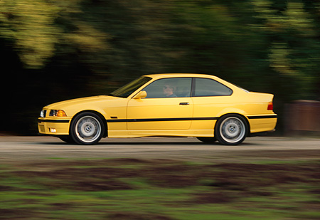 AUT 29 RK0015 05 © Kimball Stock 1995 BMW M3 Yellow 3/4 Front View On Road In Motion