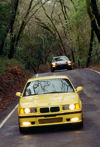 AUT 29 RK0019 07 © Kimball Stock 1995 BMW M3 Yellow Head On View On Road In Motion By Trees