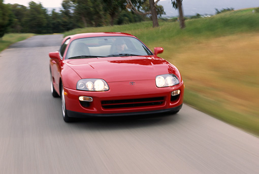 AUT 29 RK0035 01 © Kimball Stock 1997 Toyota Supra 15th Anniversary Edition Red 3/4 Front View On Road In Motion