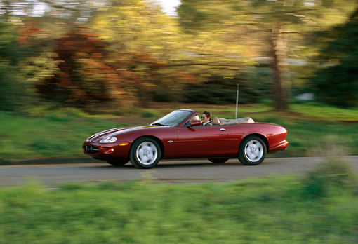 AUT 29 RK0040 19 © Kimball Stock 1997 Jaguar XK8 Convertible Red 3/4 Side View On Road In Motion By Trees