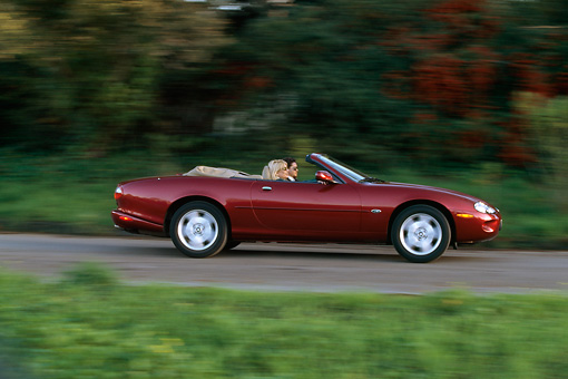 AUT 29 RK0041 10 © Kimball Stock 1997 Jaguar XK8 Convertible Red Profile View On Road In Motion