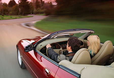 AUT 29 RK0042 03 © Kimball Stock 1997 Jaguar XK8 Convertible Red In Motion On Road With Driver And Passenger