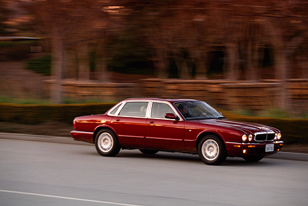 AUT 29 RK0046 01 © Kimball Stock 1998 Jaguar XJ8 Red 3/4 Side View On Road In Motion