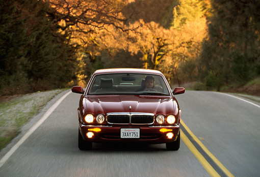 AUT 29 RK0048 20 © Kimball Stock 1998 Jaguar XJ8 Red Head On View On Road In Motion By Trees