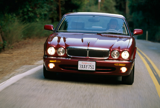 AUT 29 RK0048 32 © Kimball Stock 1998 Jaguar XJ8 Red Head On View On Road In Motion By Trees