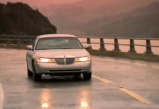 AUT 29 RK0068 04 © Kimball Stock 1998 Lincoln Town Car Silver 3/4 Front View On Wet Road In Motion