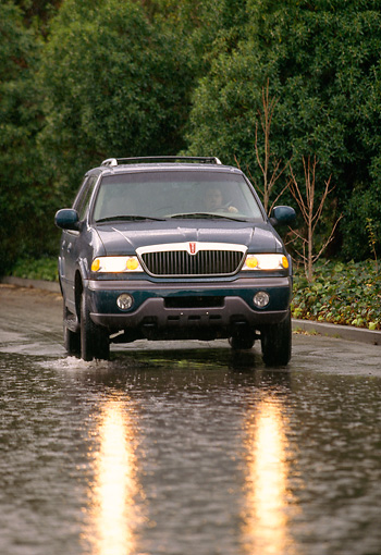 AUT 29 RK0093 01 © Kimball Stock 1998 Lincoln Navigator Green Head On View On Road In Motion