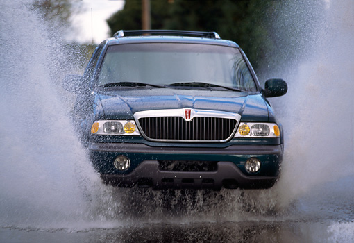 AUT 29 RK0102 01 © Kimball Stock 1998 Lincoln Navigator Green Splashing Water Head On View In Motion