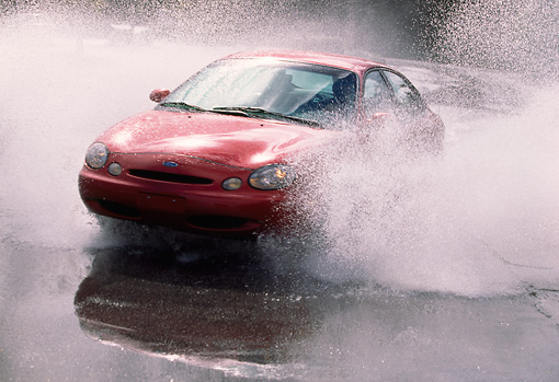 AUT 29 RK0114 01 © Kimball Stock 1998 Ford Taurus GL Red 3/4 Front View Splashing Water In Motion