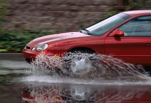 AUT 29 RK0119 01 © Kimball Stock 1998 Ford Taurus GL Red Profile Splashing Water In Motion