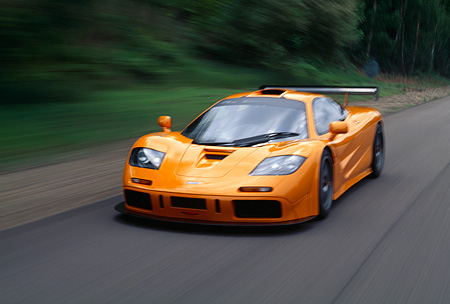 AUT 29 RK0124 15 © Kimball Stock 1996 McLaren F1 LM Orange In Motion 3/4 Front View On Road By Grass And Trees