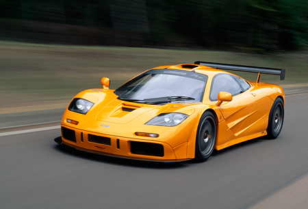 AUT 29 RK0124 16 © Kimball Stock 1996 McLaren F1 LM Orange In Motion 3/4 Front View On Road By Grass And Trees