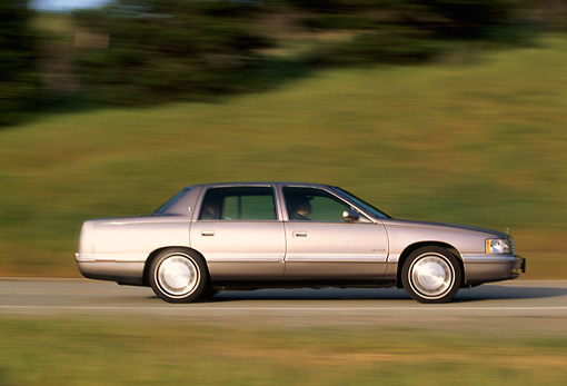 AUT 29 RK0128 01 © Kimball Stock 1998 Cadillac De Ville Champagne Profile View On Road In Motion