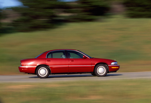 AUT 29 RK0133 01 © Kimball Stock 1999 Buick Park Avenue Red Profile View On Road In Motion
