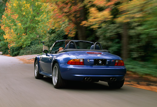 AUT 29 RK0165 02 © Kimball Stock 1999 BMW M Roadster Z3 Convertible Blue 3/4 Rear View On Road In Motion