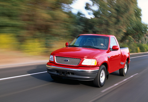 AUT 29 RK0207 04 © Kimball Stock 1999 Ford F150 Lariat Triton V8 Red 3/4 Front View On Road In Motion