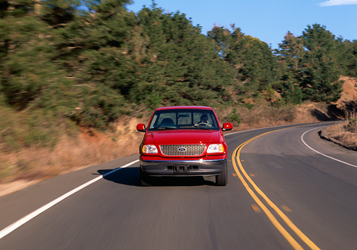 AUT 29 RK0208 01 © Kimball Stock 1999 Ford F150 Lariat Triton V8 Red Head On View On Road In Motion By Trees