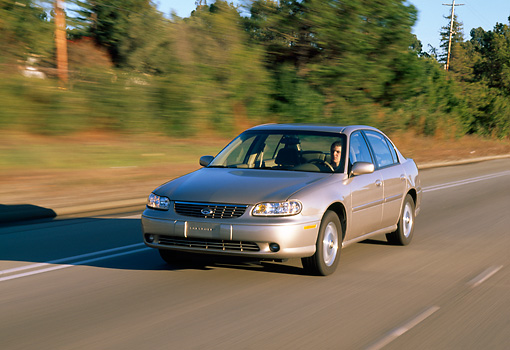 AUT 29 RK0216 05 © Kimball Stock 1999 Chevrolet Malibu Champagne Front 3/4 View On Road In Motion By Trees Background