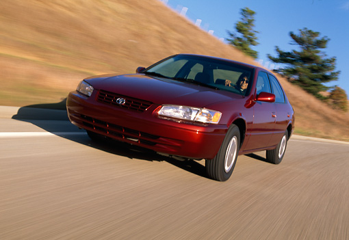 AUT 29 RK0224 01 © Kimball Stock 1999 Toyota Camry CE Red 3/4 Front View On Road In Motion