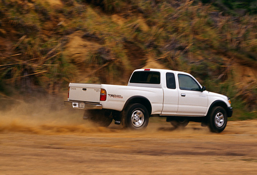 AUT 29 RK0371 08 © Kimball Stock 1999 Toyota Tacoma X-Tra 4x4 White 3/4 Rear View On Dirt Road In Motion