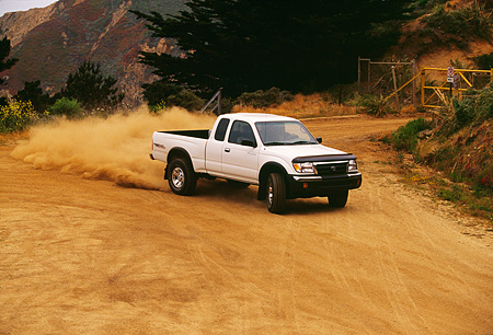 AUT 29 RK0374 08 © Kimball Stock 1999 Toyota Tacoma X-Tra 4x4 White 3/4 Front View On Dirt Road In Motion