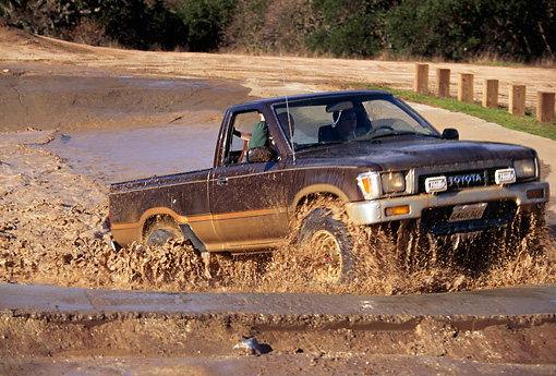 AUT 29 RK0379 11 © Kimball Stock 1981 Toyota 4x4 Pickup Truck In Motion Driving Through Mud