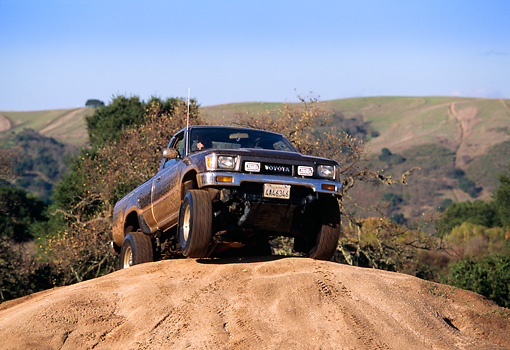 AUT 29 RK0382 02 © Kimball Stock 1981 Toyota 4x4 Pickup Truck On Dirt Hill In Motion