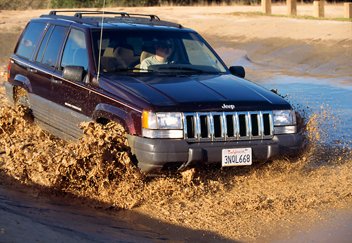 AUT 29 RK0386 07 © Kimball Stock 1996 Jeep Cherokee Burgundy Front 3/4 View In Motion Through Muddy Water