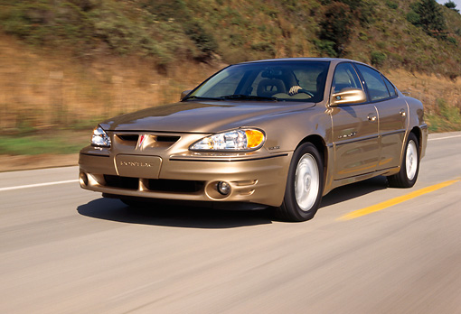 AUT 29 RK0444 02 © Kimball Stock 1999 Pontiac Grand Am Gold Low 3/4 Front View On Road In Motion