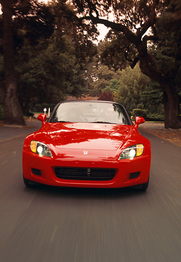 AUT 29 RK0467 01 © Kimball Stock 2000 Honda S2000 Convertible Red Head On View On Road In Motion By Trees
