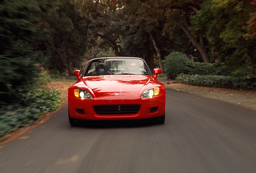 AUT 29 RK0467 07 © Kimball Stock 2000 Honda S2000 Convertible Red Head On View On Road In Motion By Trees