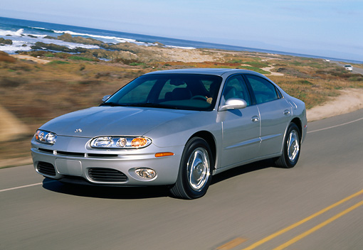 AUT 29 RK0486 08 © Kimball Stock 2001 Oldsmobile Aurora V8 Silver 3/4 Front View On Road By Ocean