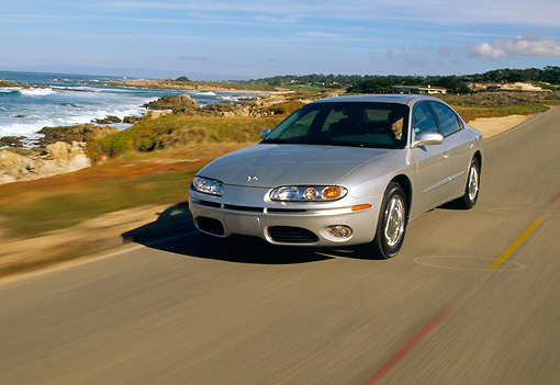 AUT 29 RK0486 34 © Kimball Stock 2001 Oldsmobile Aurora V8 Silver 3/4 Front View On Road By Ocean