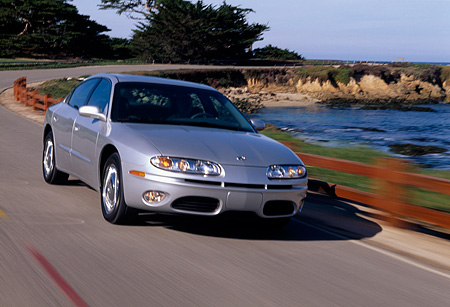 AUT 29 RK0488 03 © Kimball Stock 2001 Oldsmobile Aurora V8 Silver 3/4 Front View On Road In Motion By Water