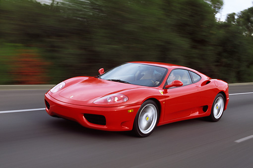 AUT 29 RK0495 01 © Kimball Stock 1999 Ferrari 360 Modena Red In Motion On Road 3/4 Front View Trees