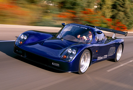 AUT 29 RK0512 12 © Kimball Stock 2000 Ultima GTR Blue 3/4 Front View On Road In Motion Blurry Trees