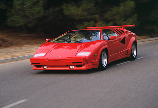 AUT 29 RK0527 05 © Kimball Stock 1989 Lamborghini Countach 25th Anniversary Edition Red 3/4 Front View On Road In Motion
